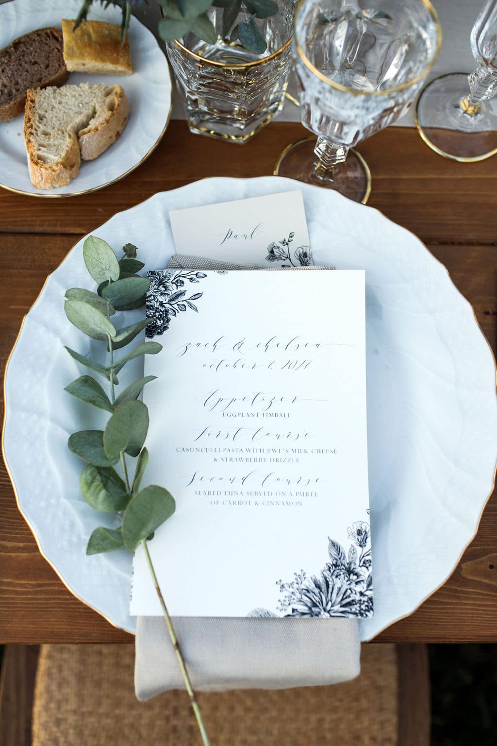 white menu and table setting with green accent plant
