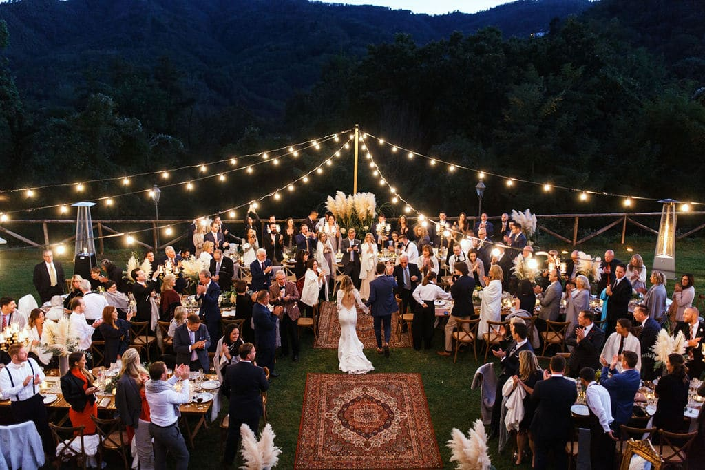 wedding party under lights around boho carpets at outdoor wedding dancing