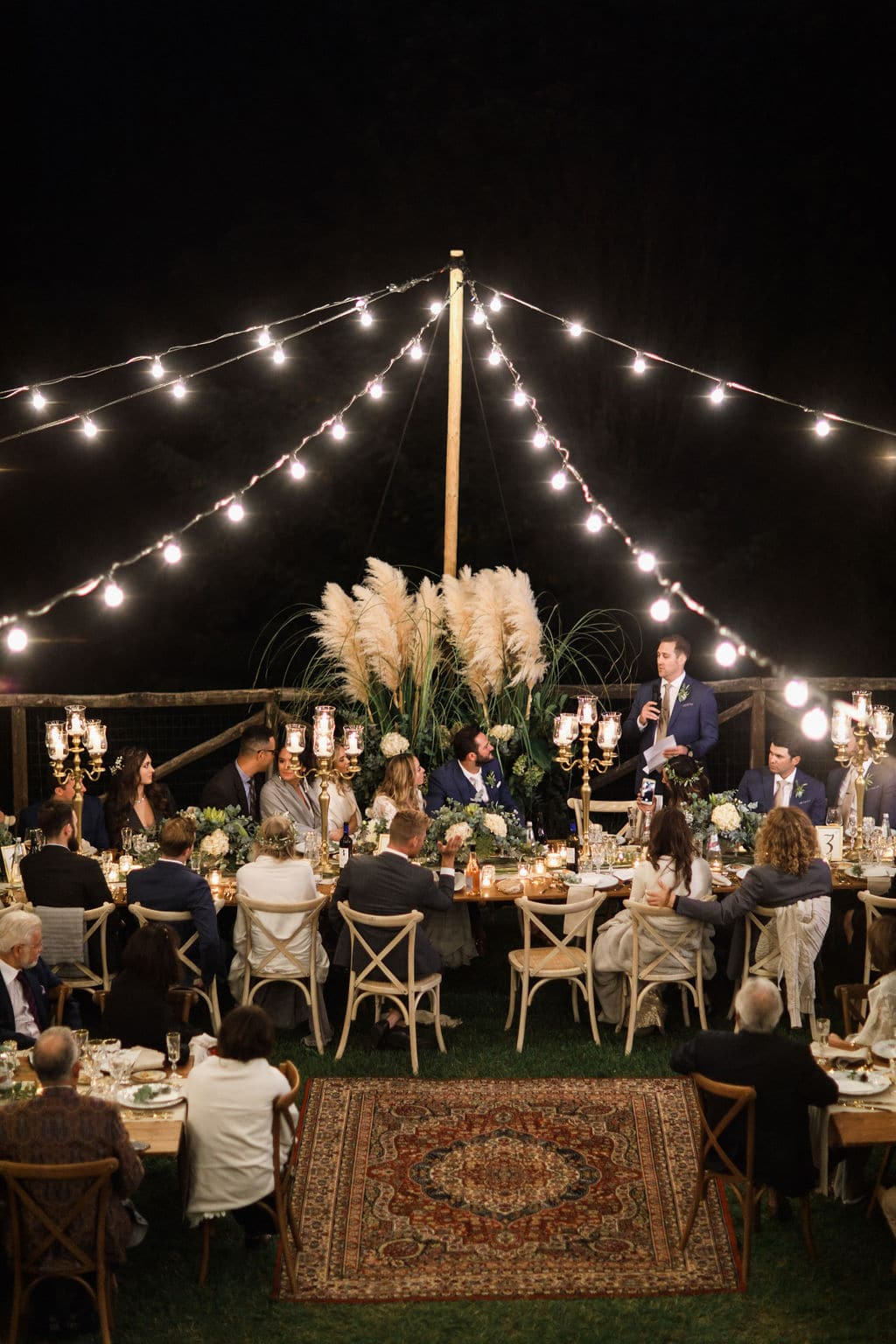 boho outdoor wedding with lights and guests seated at tables