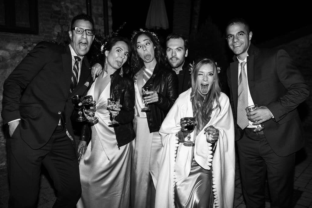black and white goofy picture of wedding party in coats outdoor wedding