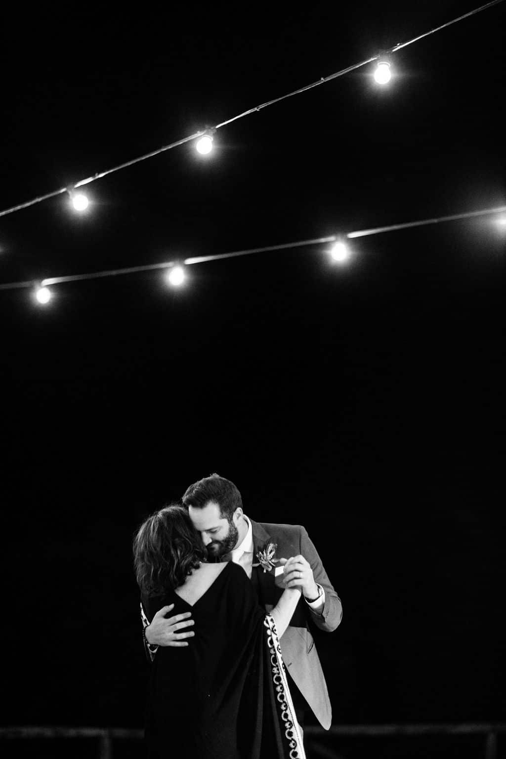 mother and groom dance in black and white outdoor wedding