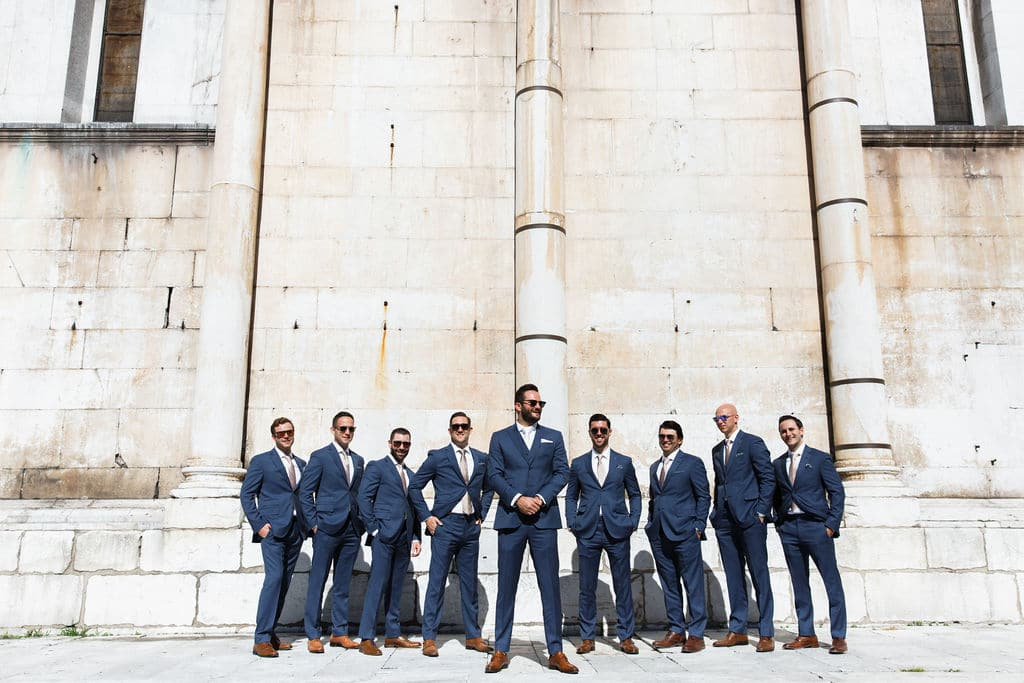 groomsmen in navy tuxedos and sunglasses before ceremony