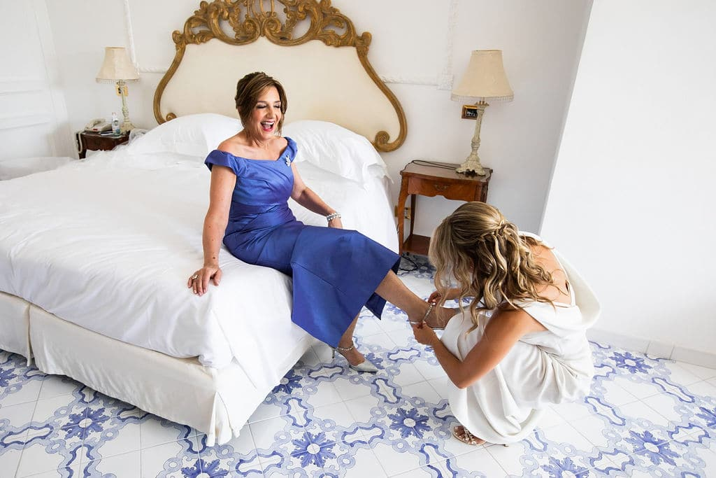 mother of the bride getting help putting her shoes on for the Italian wedding