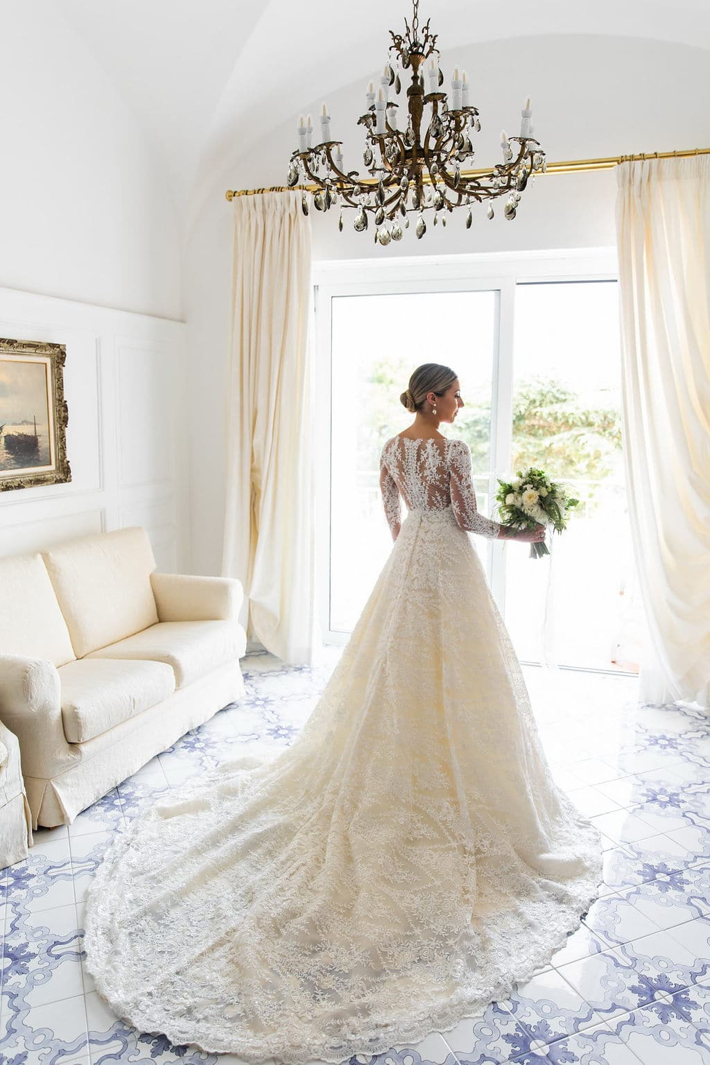 long train and lace sleeves on wedding gown with white floral bouquet