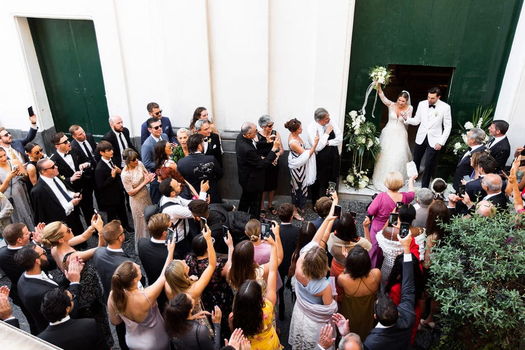 bride and groom excited leaving ceremony with Italian townspeople and wedding guests on cobble stone