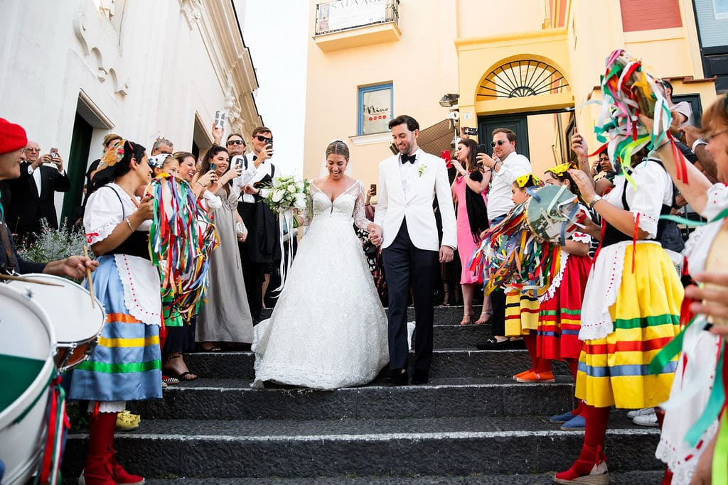 bride and groom leaving ceremony and having townspeople congratulate them in town square