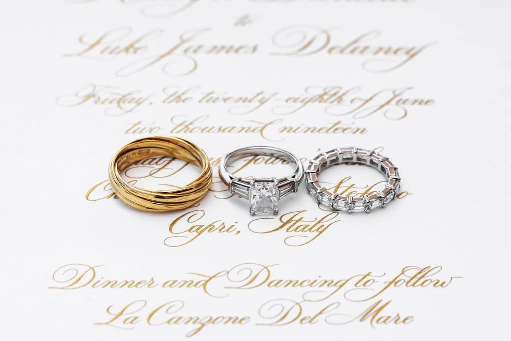 wedding bands and engagement on gold printed invitation on white paper