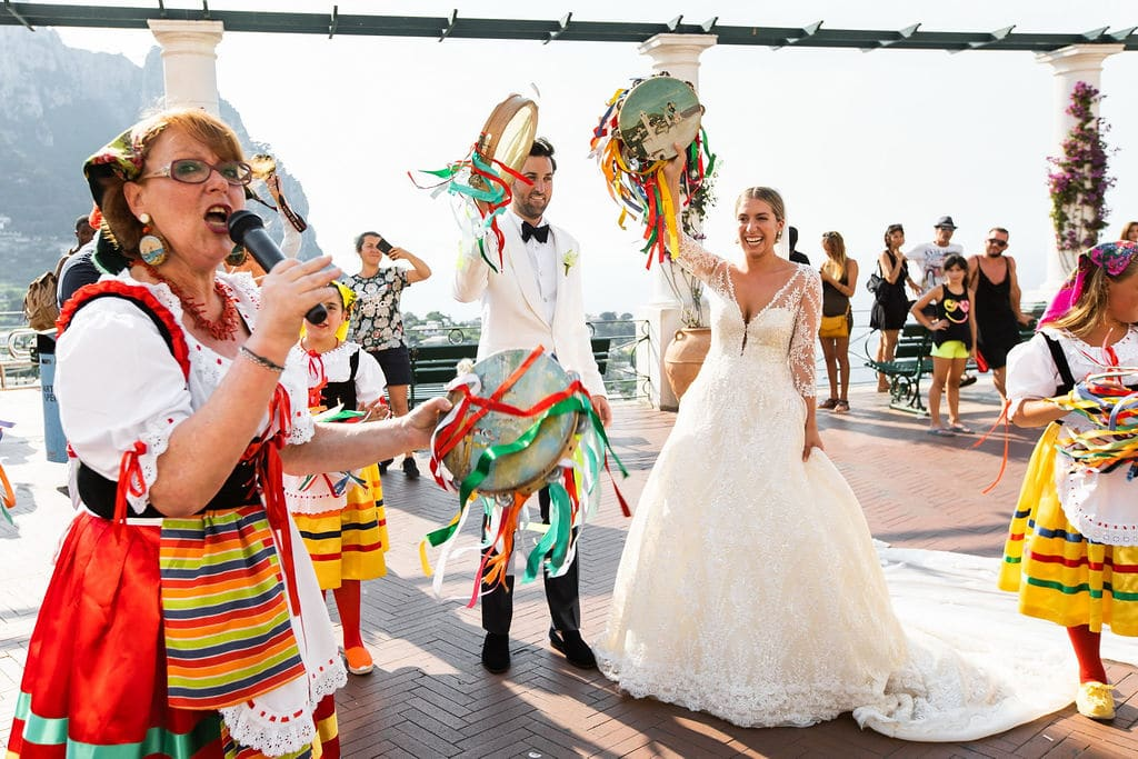 bride and groom entrance into reception in capri italy with dancers and streamers