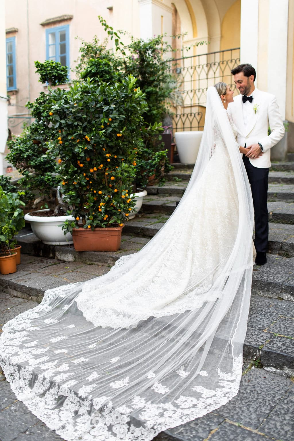 stunning long lace veil on bride kissing groom in front of bush with flowers in italy