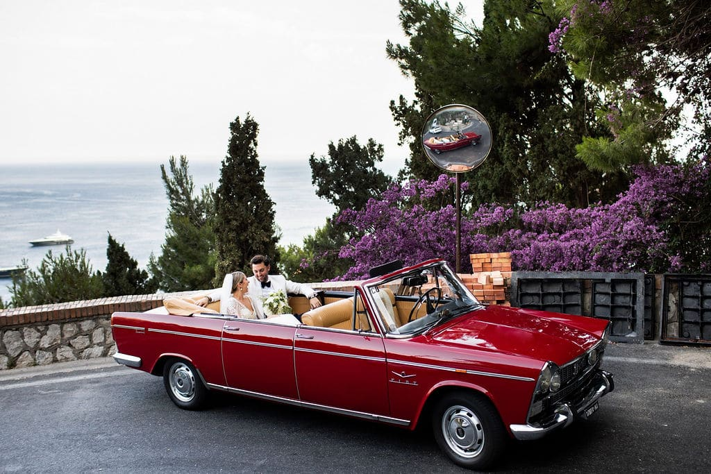 couple in back of red antique convertible after wedding ceremony in Italy