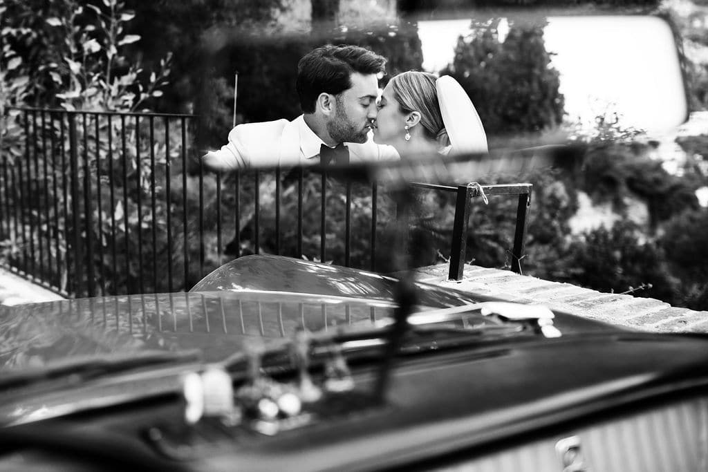 rear-view mirror photo of wedded couple kissing in vintage car