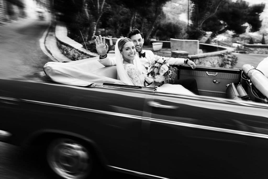 vintage car shot of bride and groom driving away after ceremony in black and white