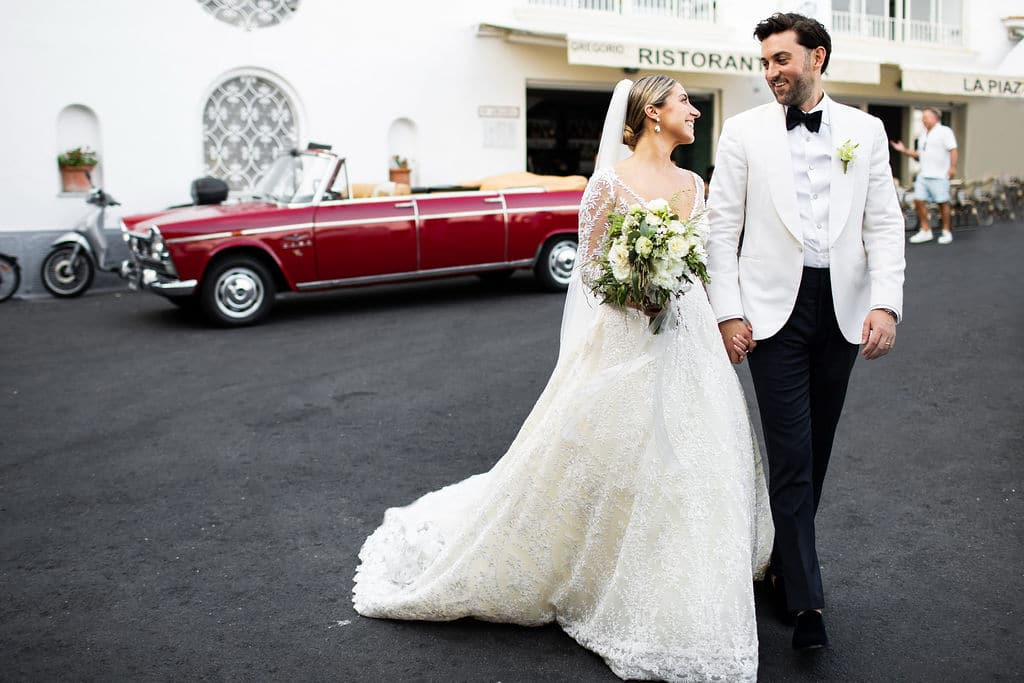 vintage car in background of bride and groom walking with white floral bouquet in bride's hands
