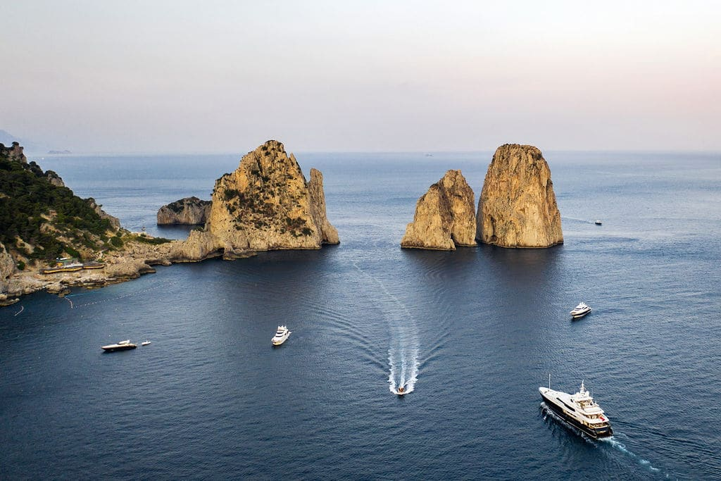renowned capri Italy rock formation with boats scattered across the blue waters