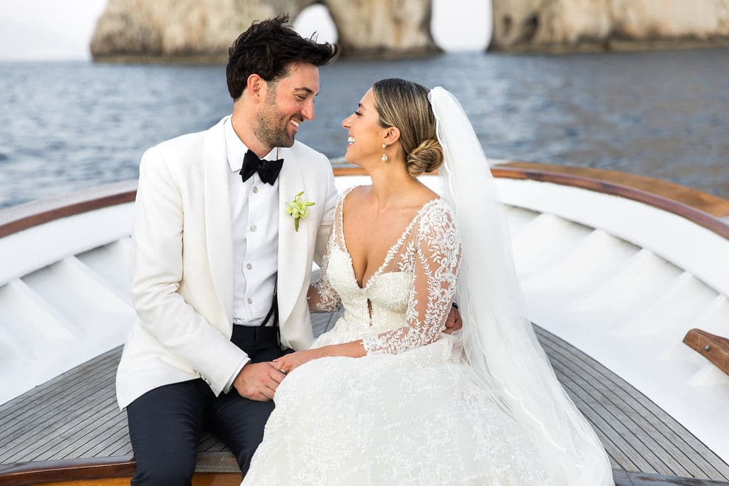 bride and groom closeup with famous capri rocks in background of post ceremony intimate boat ride
