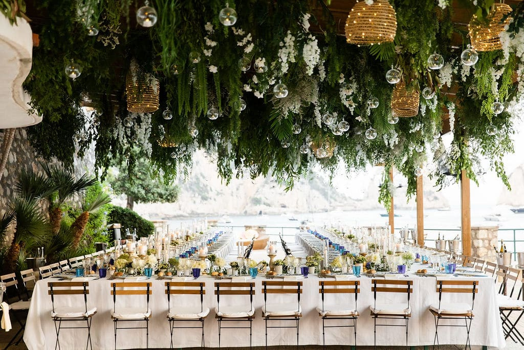 ceremony landscape with lots of flowers coating the ceiling with boho light lanterns scattered throughout the florals