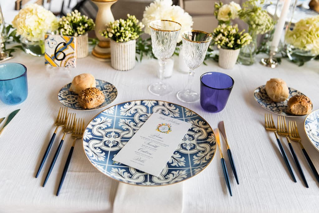 table setting with gold and blue plate with custom blue menu