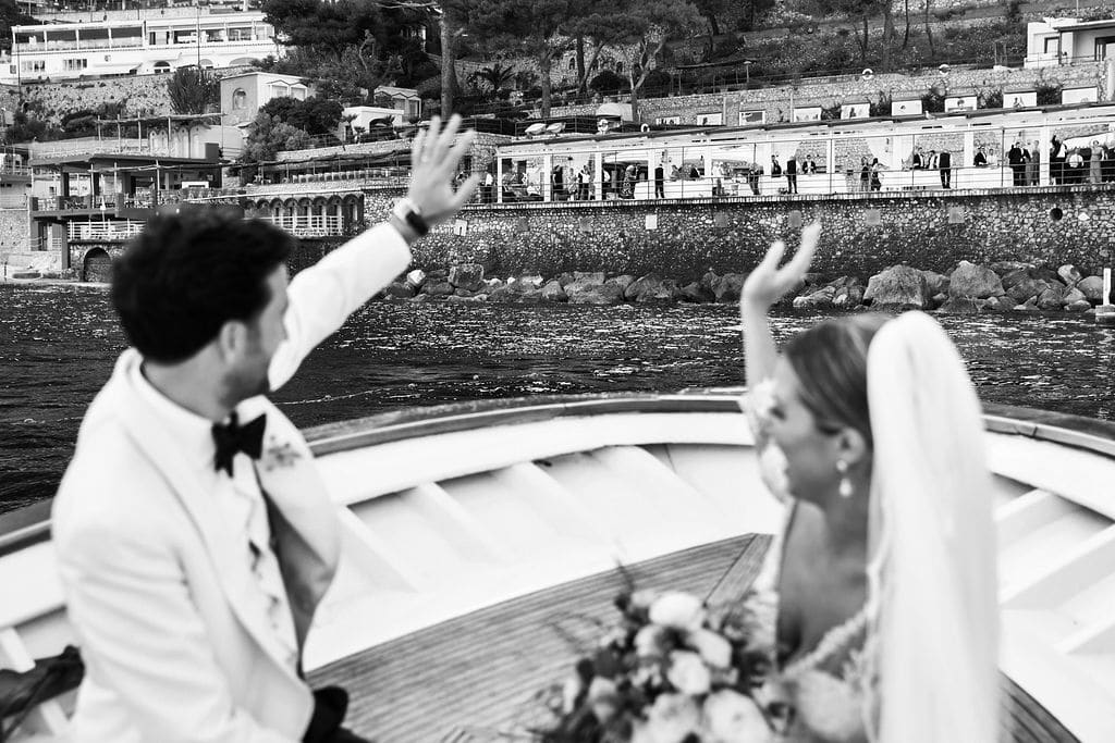 bride and groom waving to guests for a little post ceremony boat ride