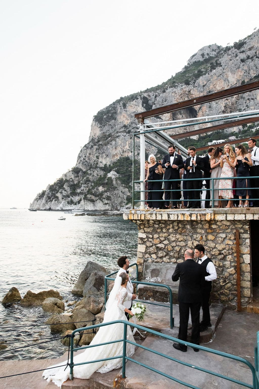 bride groom leaving ceremony with rock cliffs in Italy with guests all around