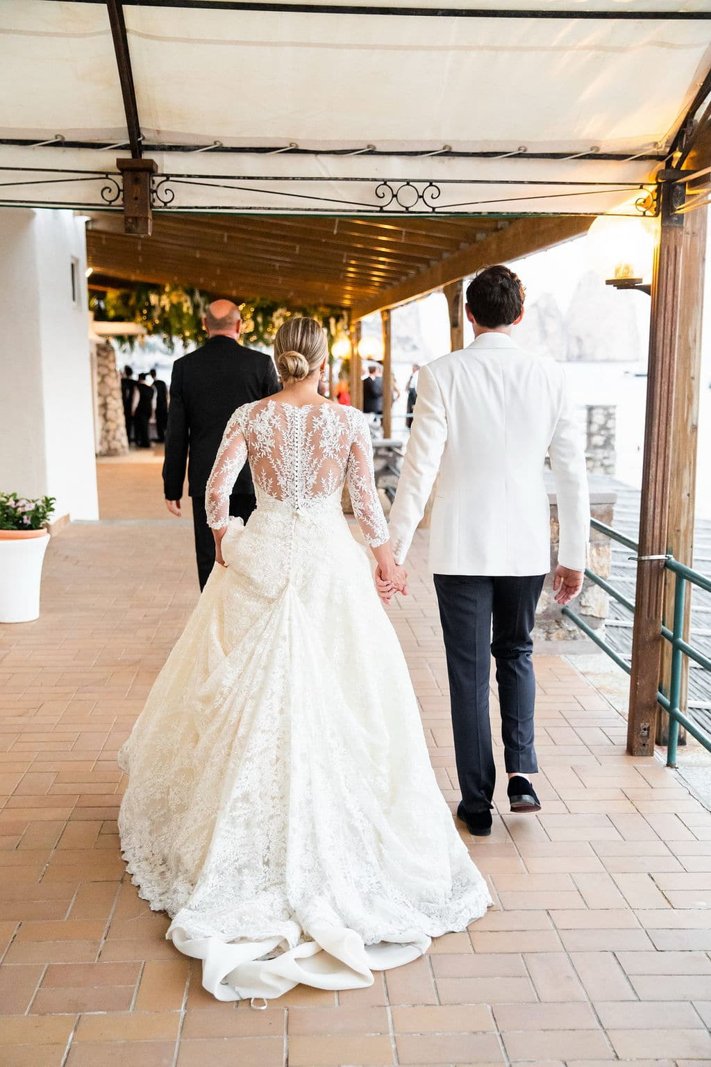 bride in lace long sleeve ball gown dress walking holding hands with groom