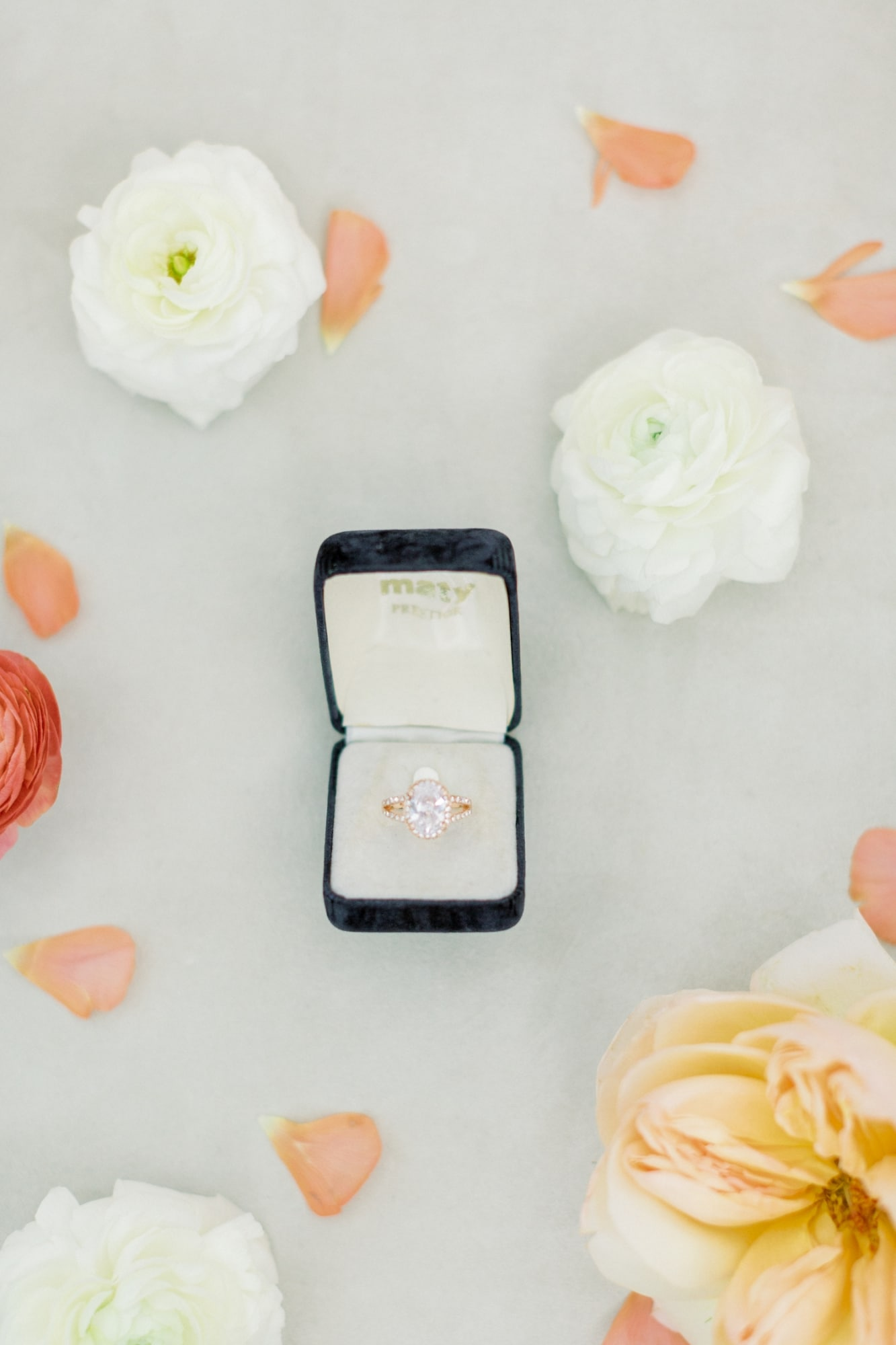 diamond ring on gold wedding band with white peach and red florals in background