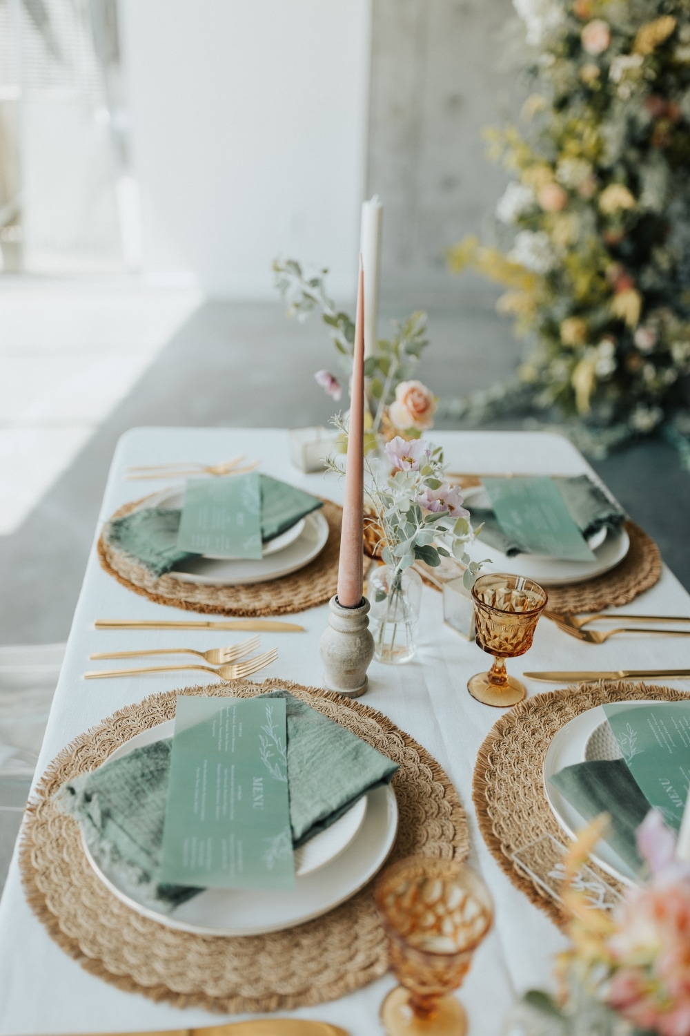 gold plates with emerald green napkins and florals in the background