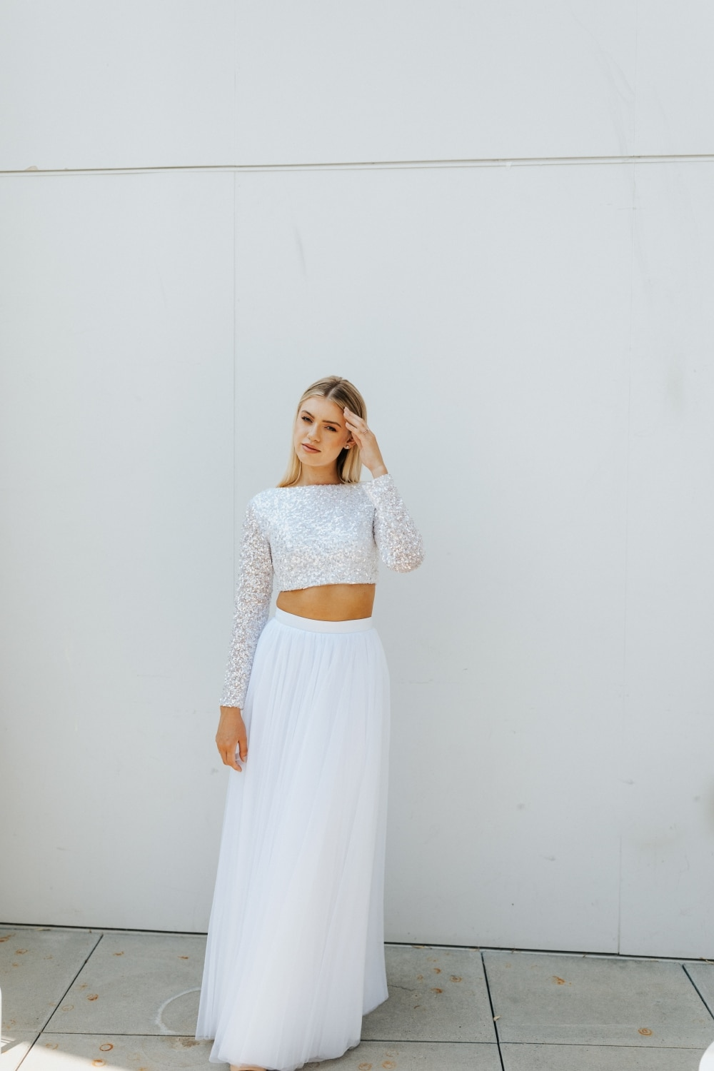 two-piece wedding gown with straight skirt with bride's hand on her face in front of white walll