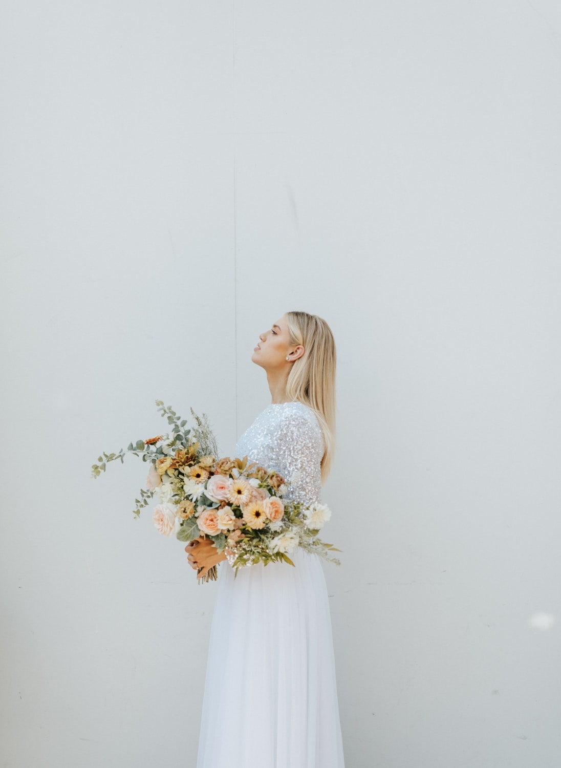 blonde bride with peach and pink florals with her head pointed up in front of white wall