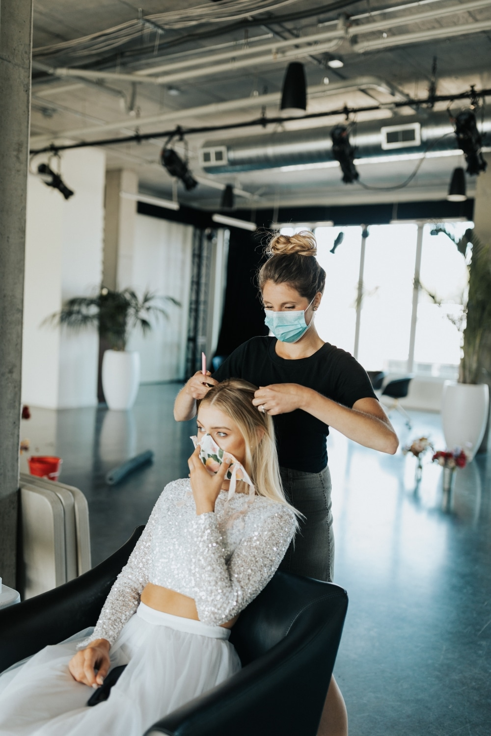 bride getting hair done with mask on both bride and hairdresser