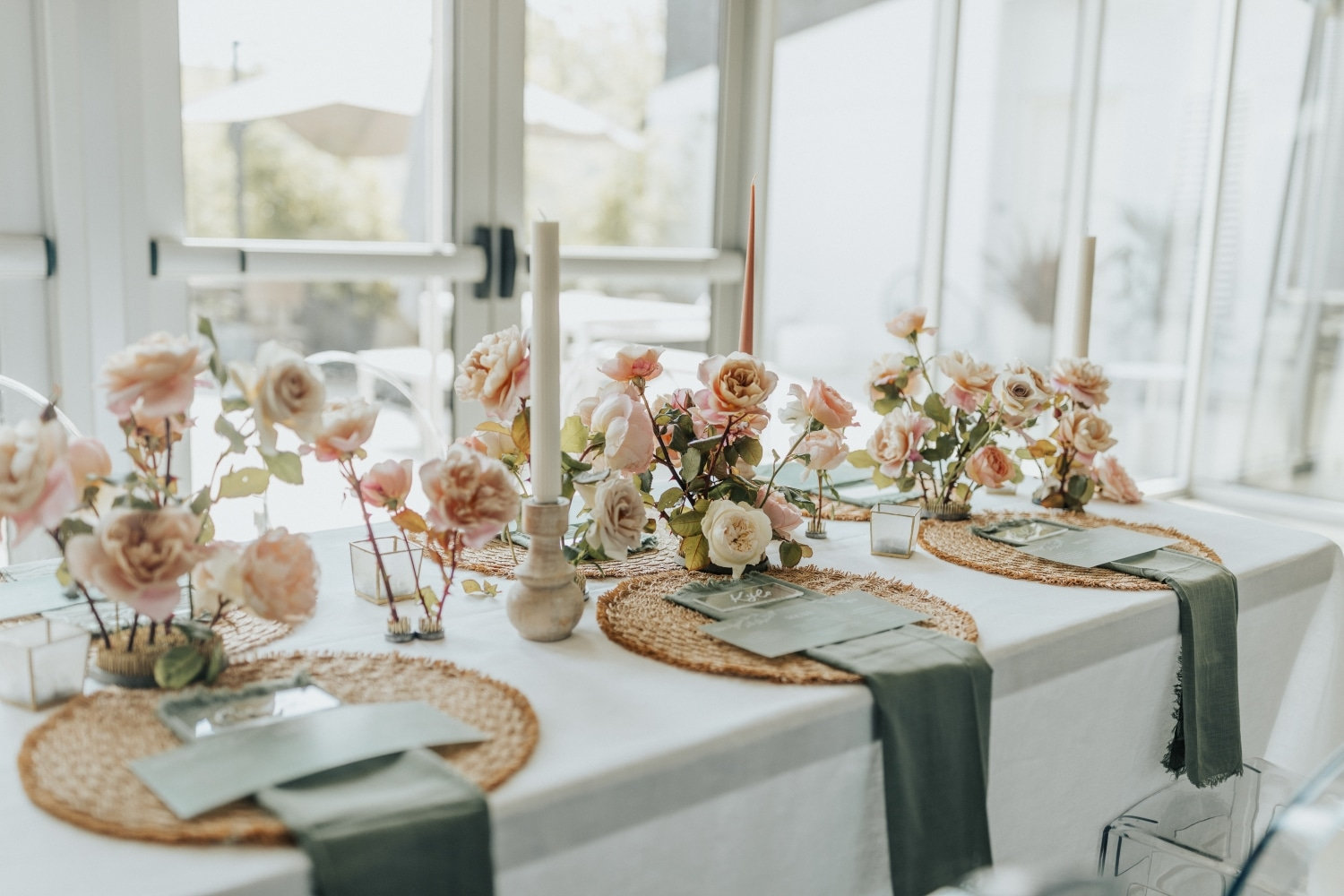 pink and peach florals as centerpieces with emerald green table