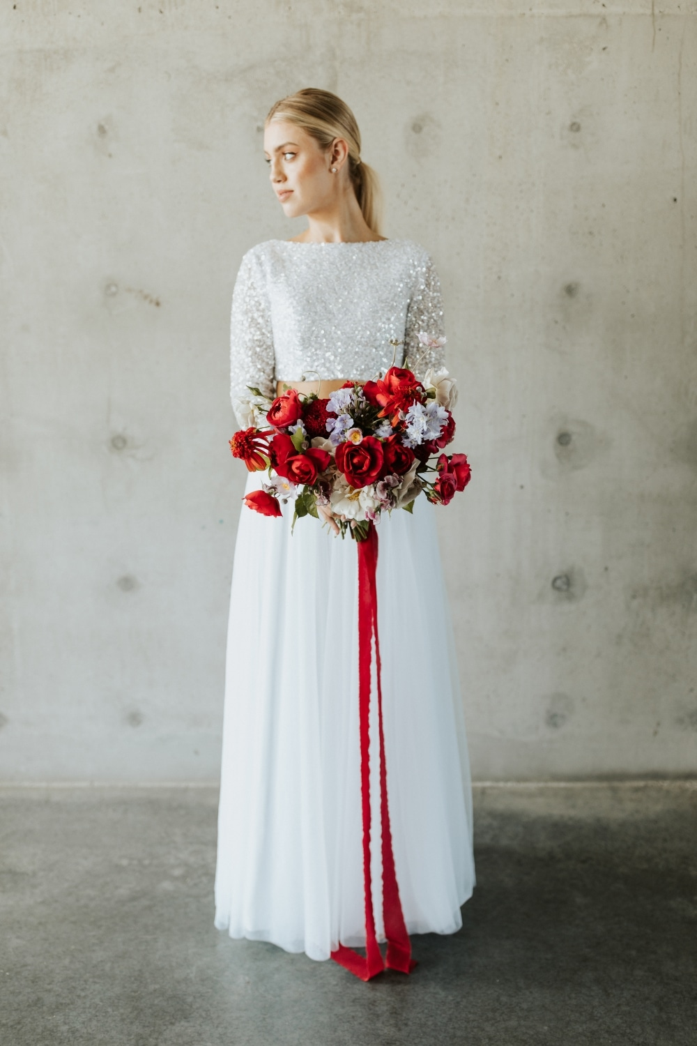 bride in two-piece wedding gown with red florals with long red ribbon