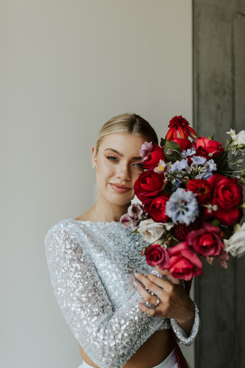closeup of bride and red florals in front of white wall