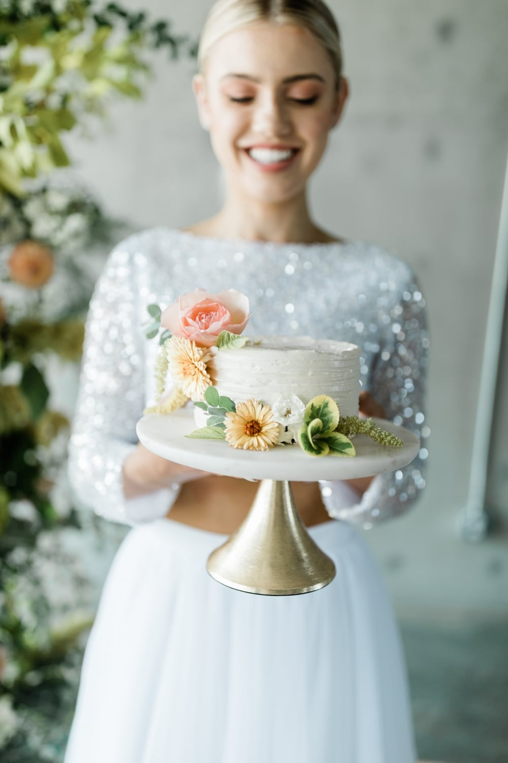 bride smiling in back of beautifully decorate one-tiered cake with florals on it