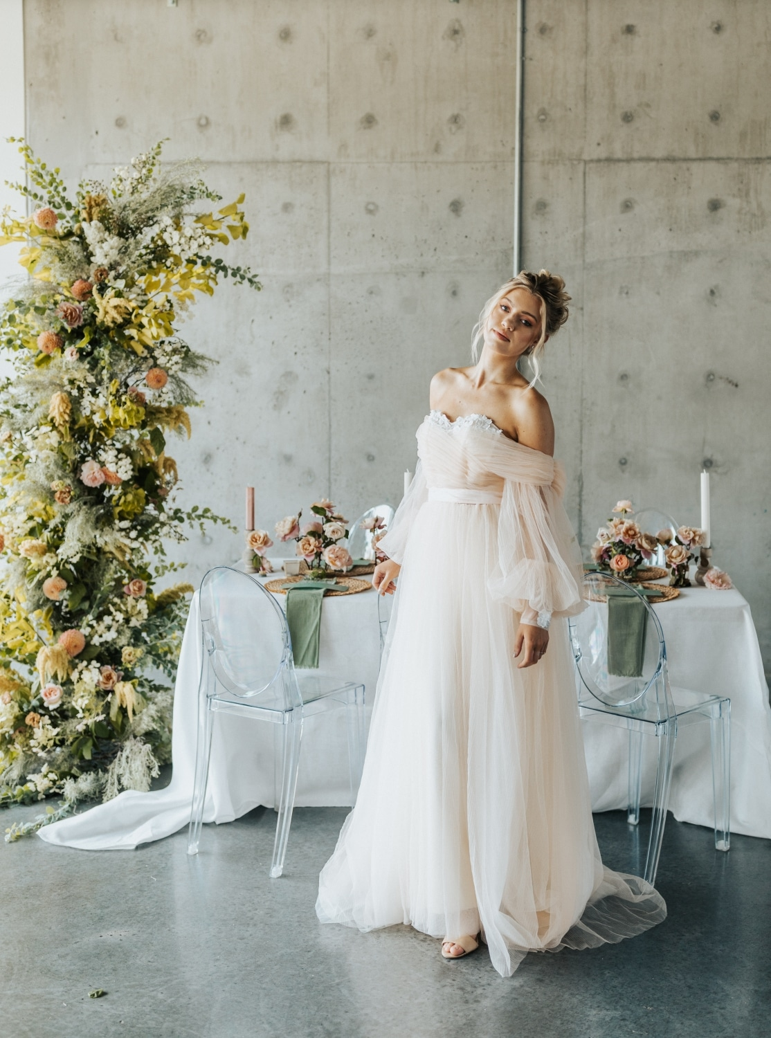 bride in front of table in a blush cream flowing dress with florals all around