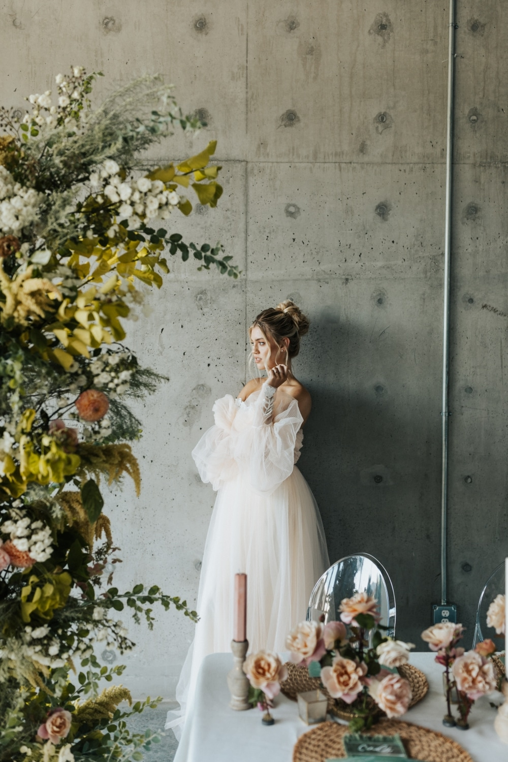 bride looking away behind table in flowers in stunning blush gown