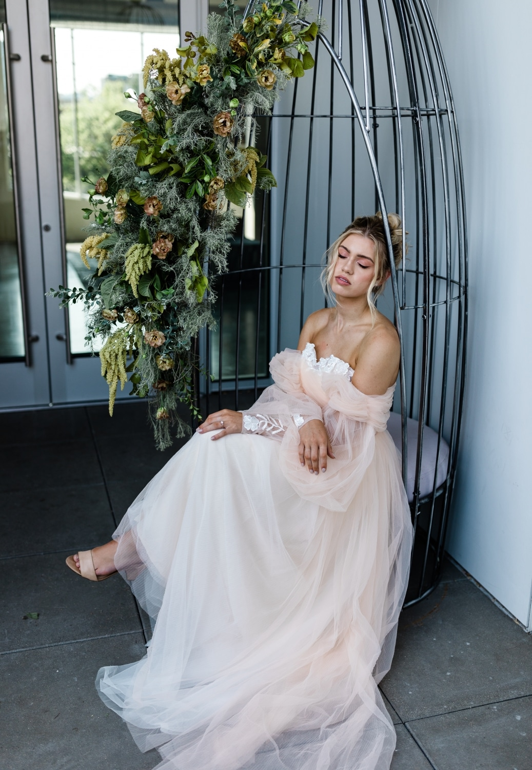 bride sitting in black cast-iron chair with beautiful flowers in the background