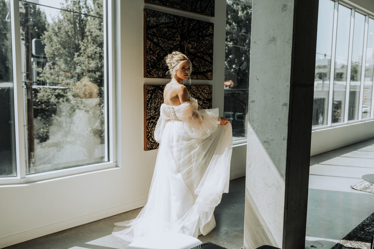 bride in hallway accentuating the long train in her flowing strapless gown