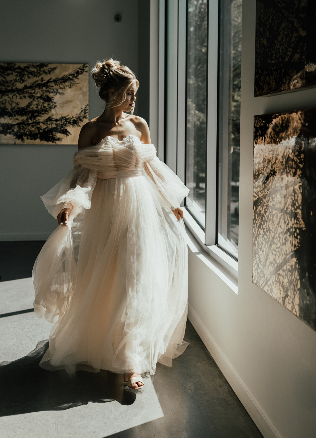 bride looking out of a window as she holds her dress to walk with an updo in her hair
