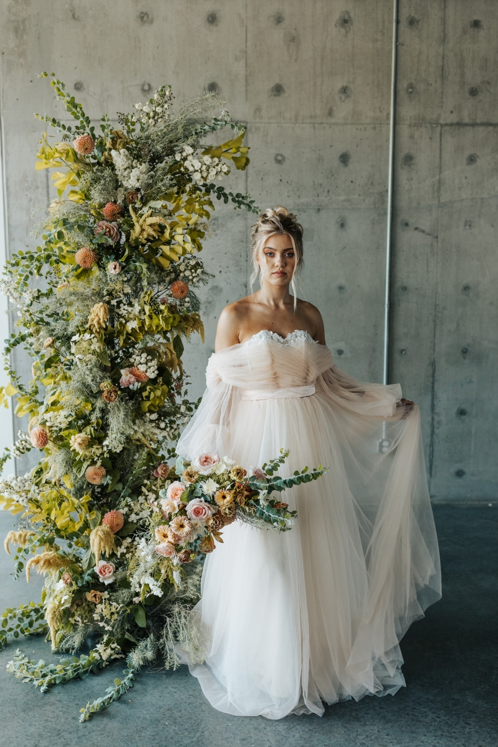 bride holding dress up in one hand and bouquet in the other