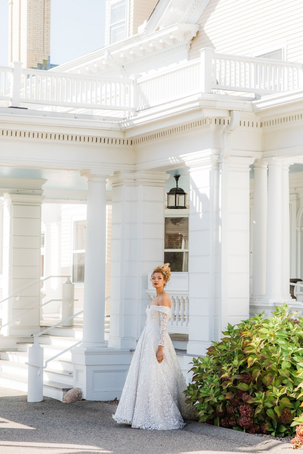 fall bride in gown wedding dress in front of stunning white mansion