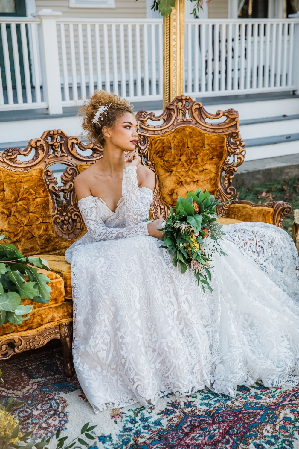 bride sitting in strapless wedding dress on copper colored couch at white mansion in fall wedding
