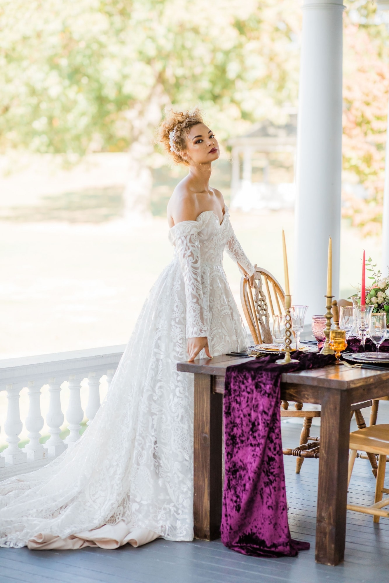 bride leaning over table setup with royal purple table runner that touches the floor