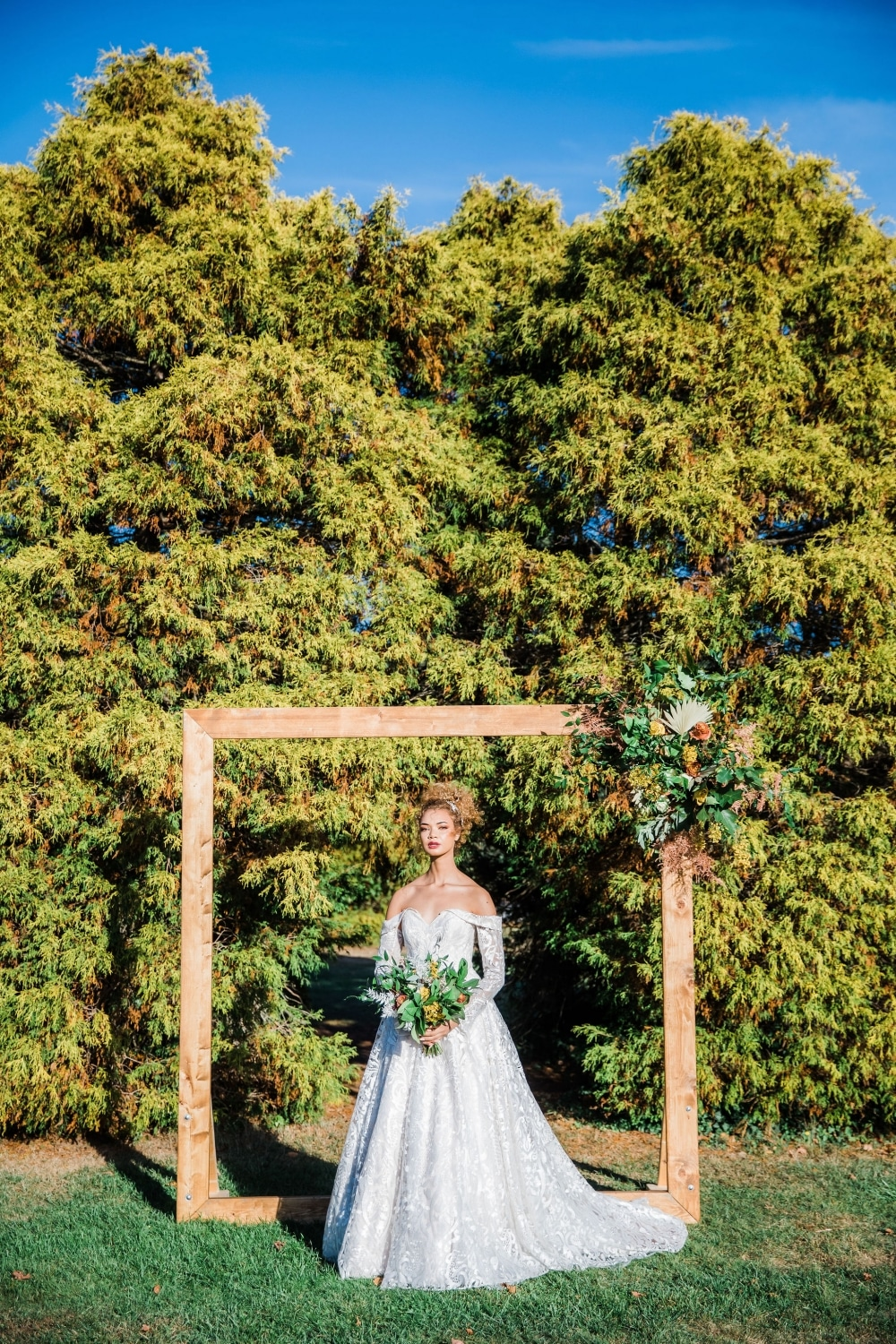 fride under altar in fall wedding with green trees in background
