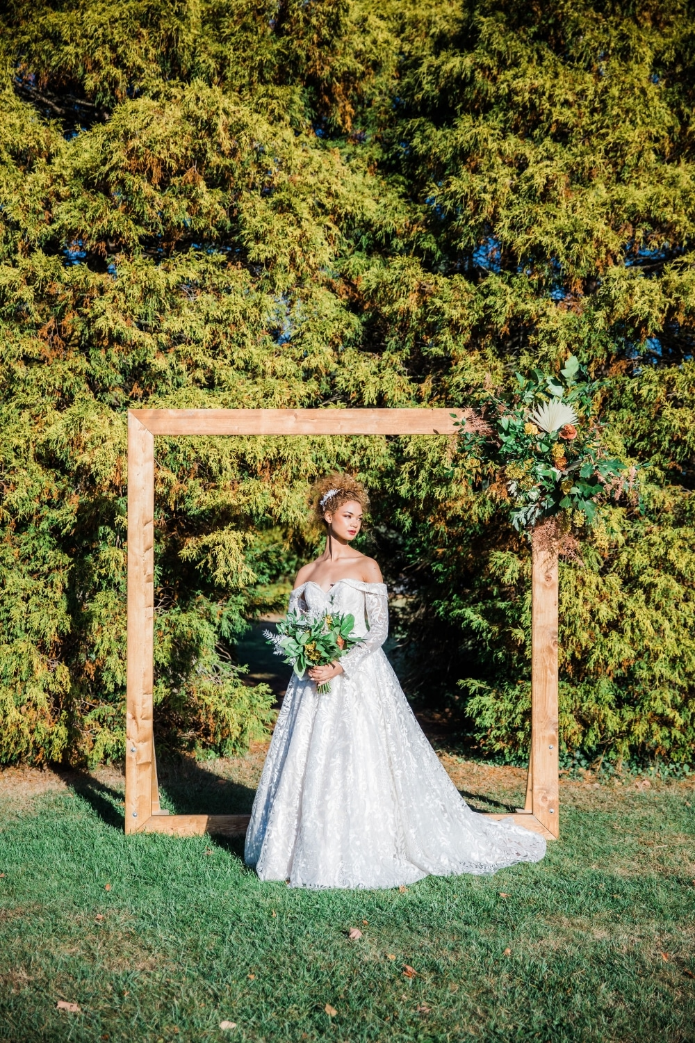bride looking away in stunning strapless wedding gown in front of altar in greenery