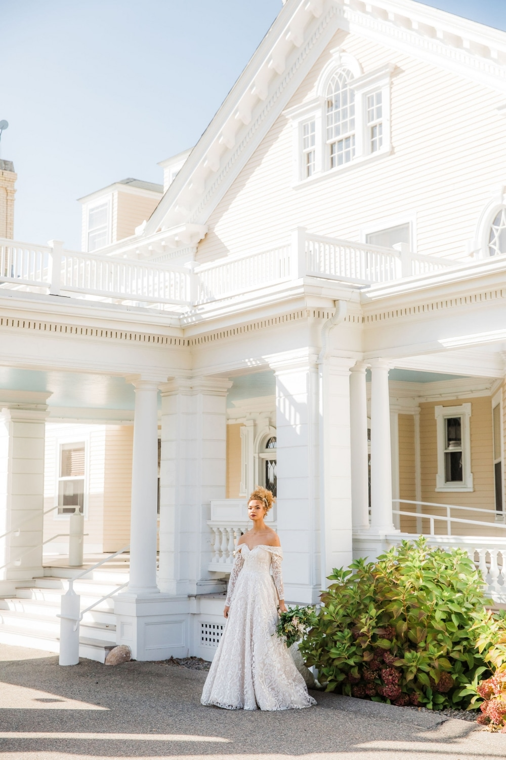 bride in front of white mansion looking beautiful