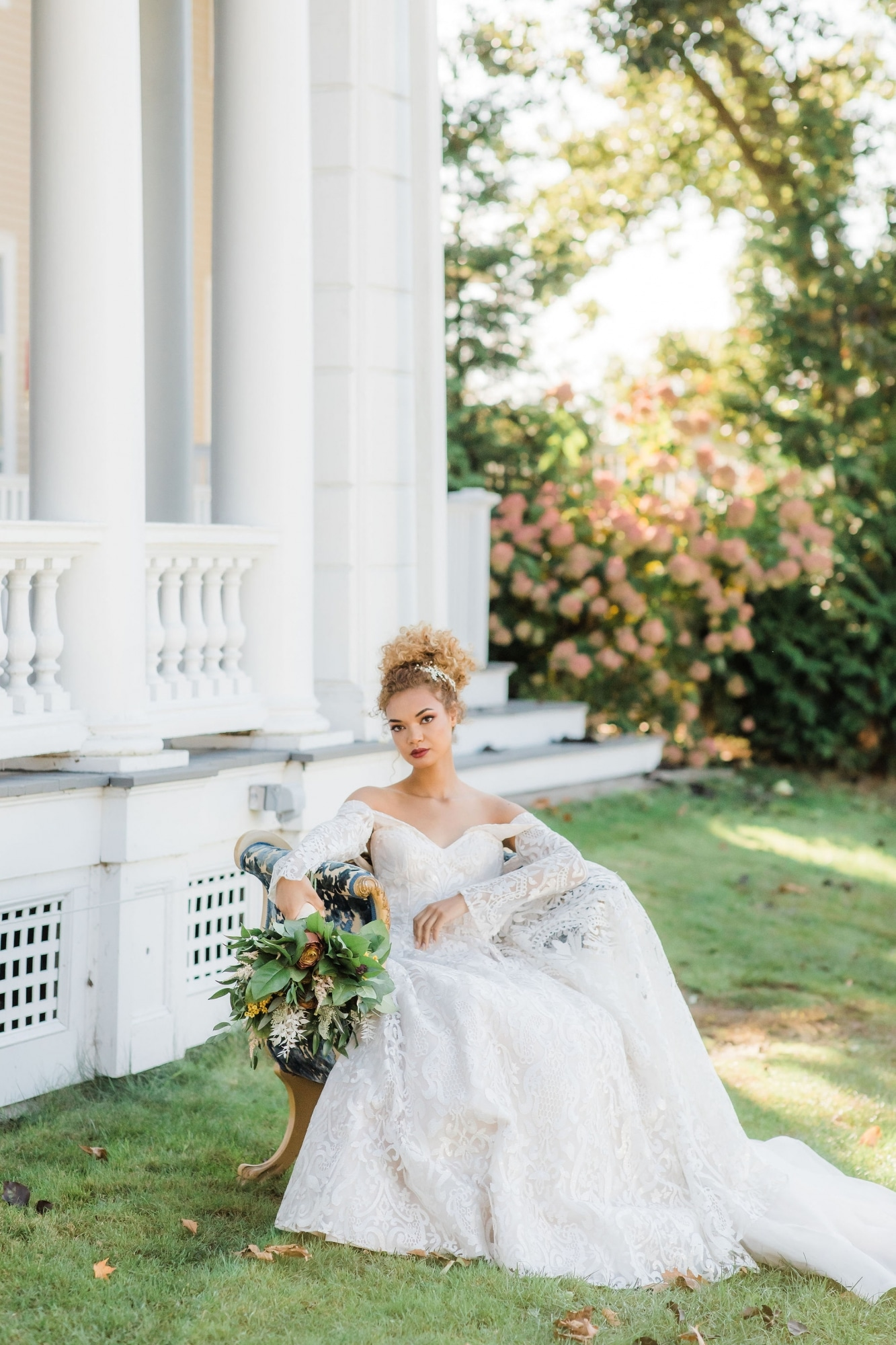 bride sitting on bench leaning over with fall floral bouquet in hand