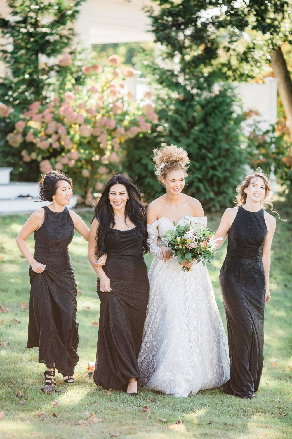 bride in white strapless ballgown smiling amongst her bridesmaids with black dresses