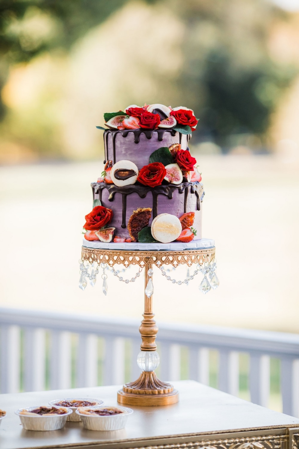 lavender cake with chocolate drip and red and pink decorated flowers