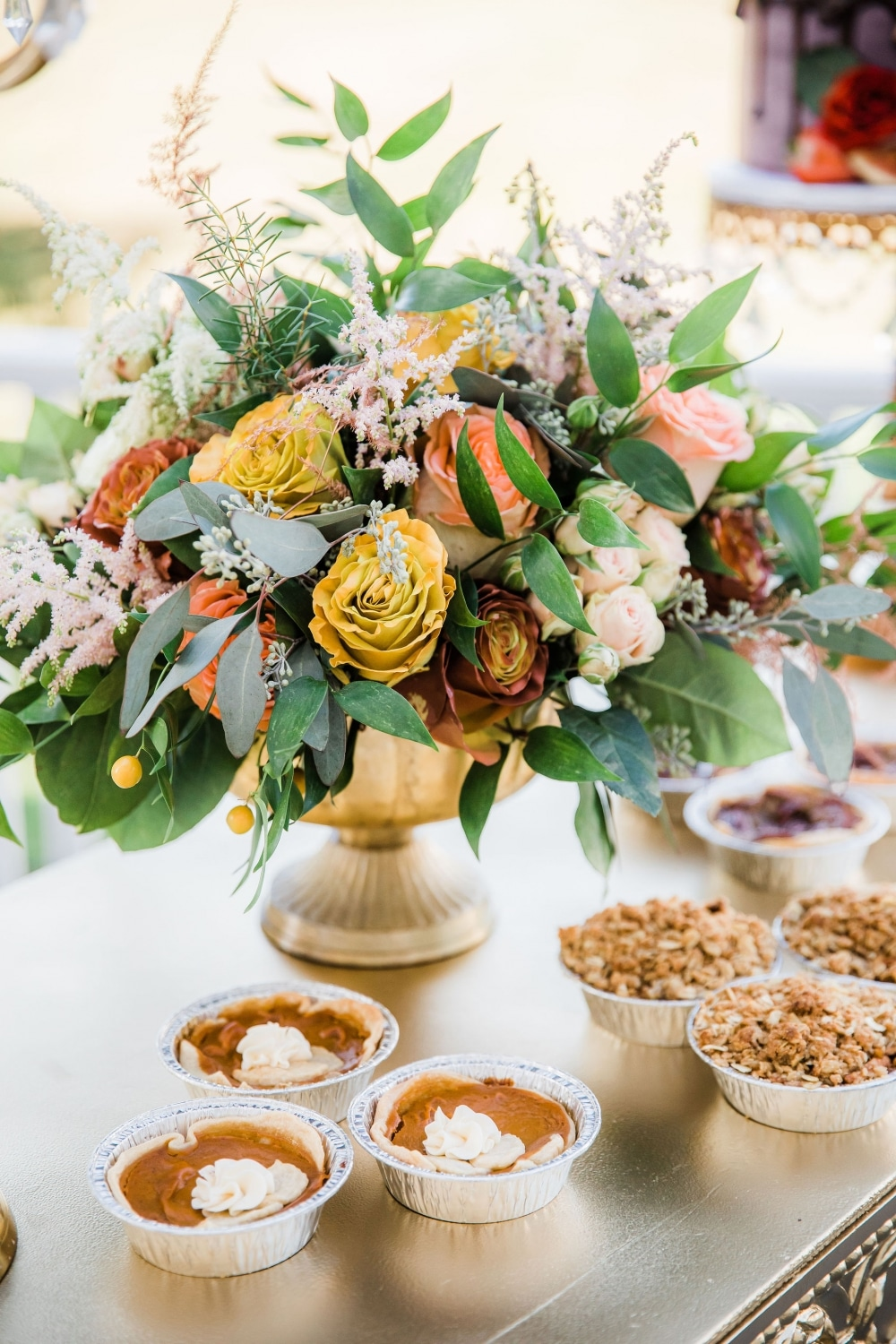 table florals with fall colors and mini pumpkin pie desserts