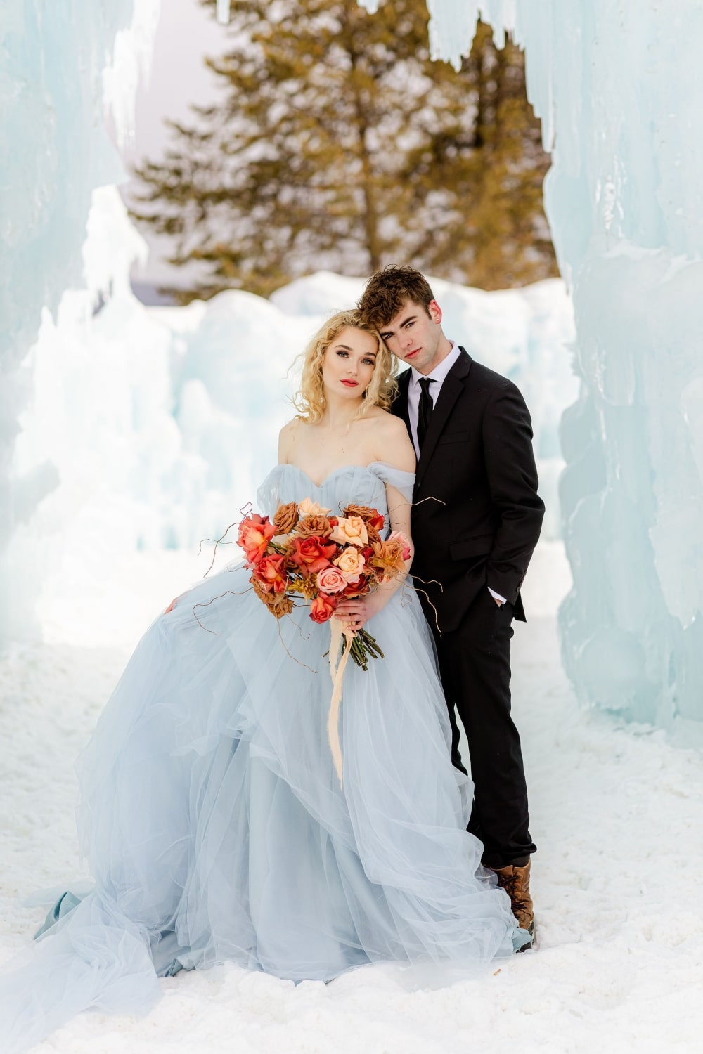 couple taking pictures at ice castle in dillon co